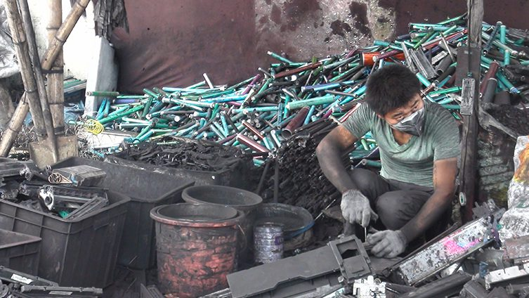 A worker dismantles e-waste
